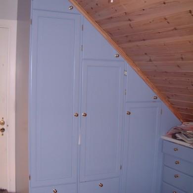 Blå garderobeskap under skråtak
