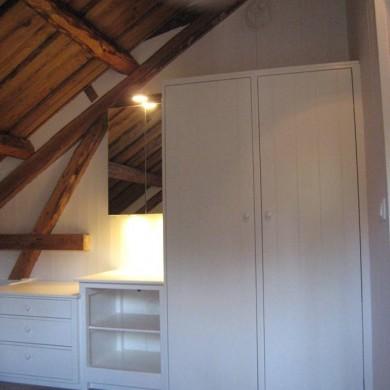 Garderobeskap, vaskeskap og nattbord under skråtak.