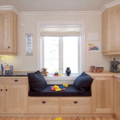 Solfjeldkjøkken i heltre bjørk med integrert sittebenk i løsningen