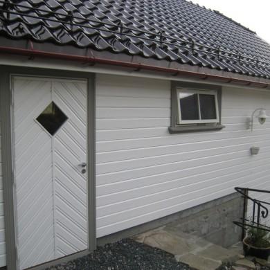 Garasje med solfjeldvinduer, fiskebenspanelt dør.